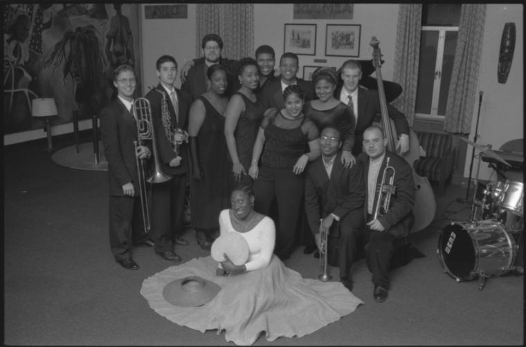 Men and women pose in a group photograph and some with various instruments.