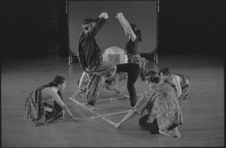 Photograph of five dancers. Three are kneeling on the stage and two are standing, face one another. Each has a leg raised that is touching the other persons and their arms are raised in the air.