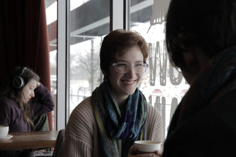 A woman smiling in a coffee shop near a window