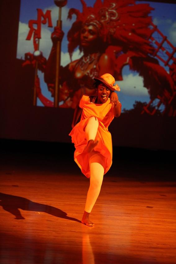 Photograph of a female dancer kicking her leg in the air.