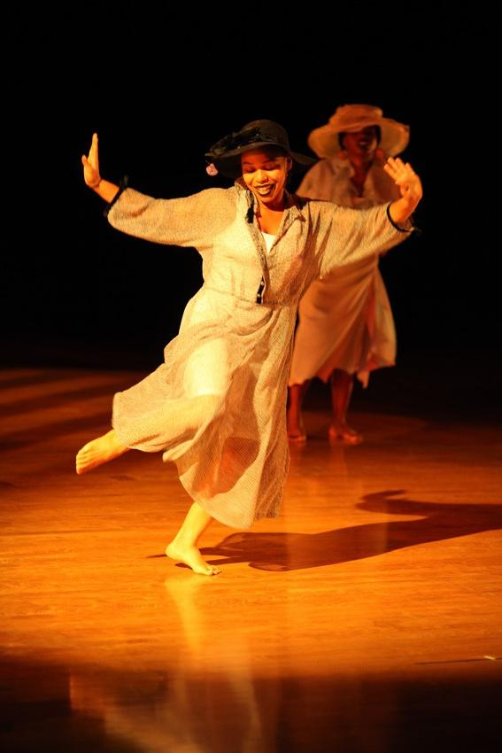 Photograph of a female dancer with her hands raised and another dancer in the background.