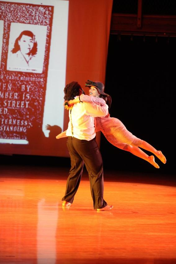 Photograph of a male dancer swinging a female dancer around.