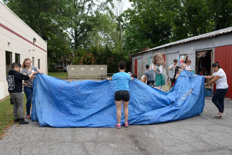 Photograph of people working with tarp material.