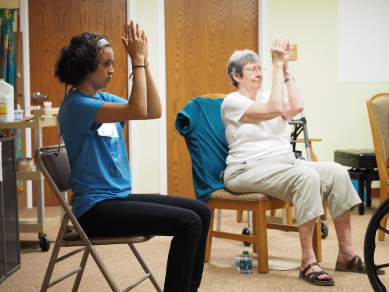 Photograph of a younger woman and an older woman exercising.