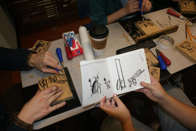 A person holds up a sketch on a piece of paper, while others carve on wood panels