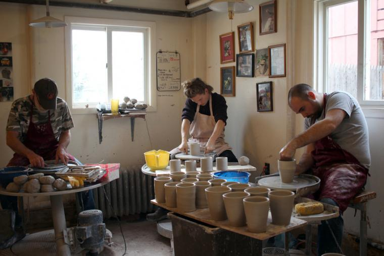 Three people work to shape clay on different potter's wheels