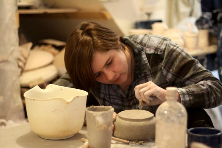 A person works with a piece of pottery
