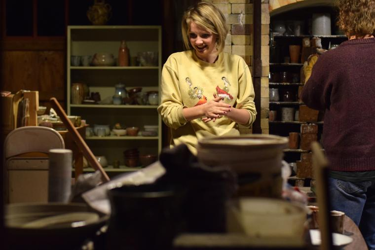 A person admires all the pottery