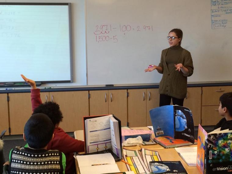 A woman gestures in front of a whiteboard while children sit at desks and one raises their hand