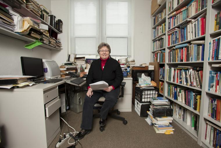 A woman sits in the middle of an office filled with files and books