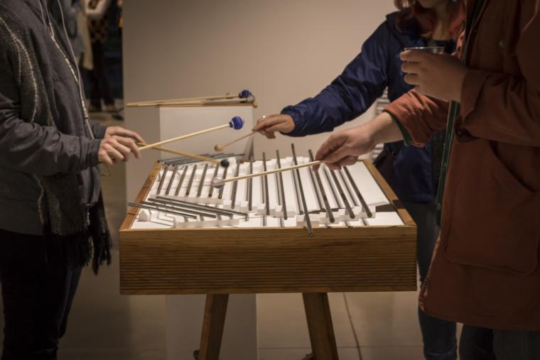 Photograph of people playing with a modular acoustic table with chimes.