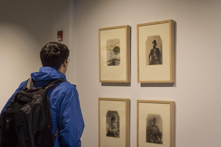 Photograph of someone looking at 4 portraits.