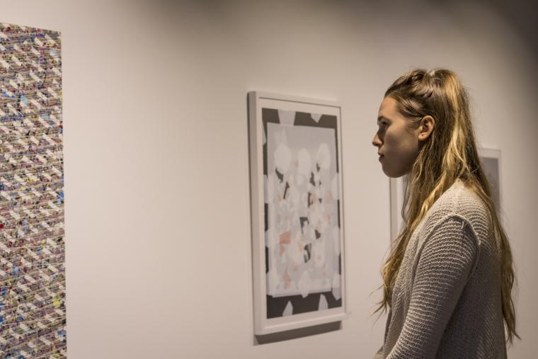Photograph of someone intensely observing a piece of artwork.