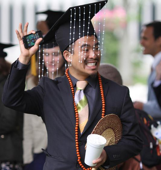 A person in commencement regalia, including a cap decorated with hanging beads