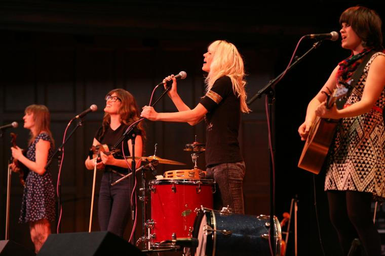 A four person band sings and performs on a stage