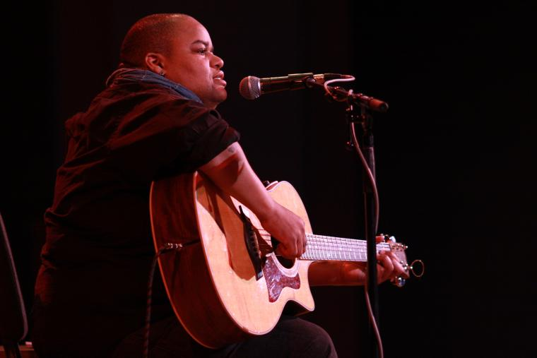 A person performs guitar and sings
