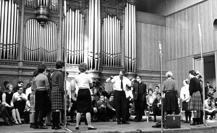 Black and white photo of people gathered on a stage