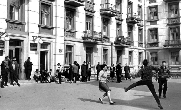 Black and white photo of three people playing frisbee in a courtyard while many others sit