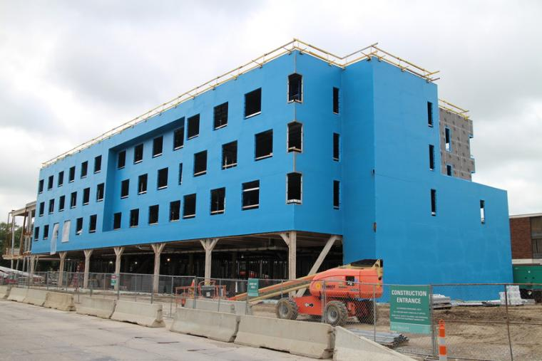 Photograph of a building that is in the middle stages of construction. The foundation and exterior walls are in place.