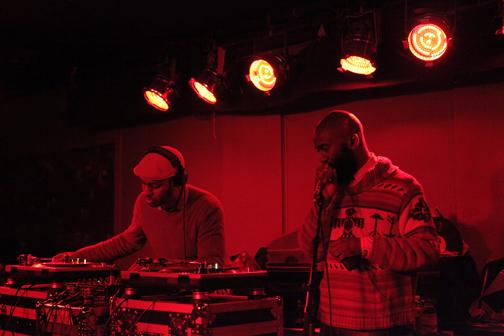 Two people DJ in red lighting