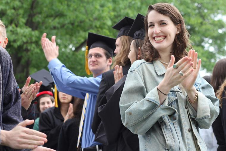 People dressed in formalwear and commencement regalia applaud