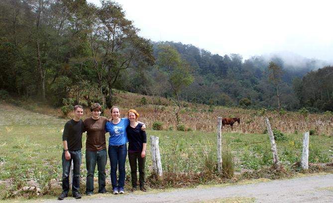 Photograph of four people posing in front a field with a horse in the background.