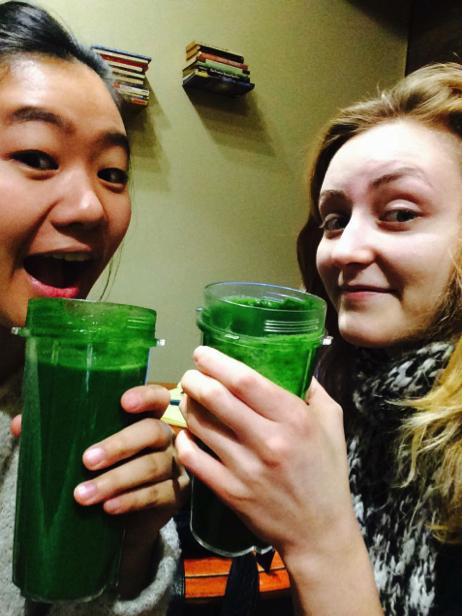 Two people hold up green drinks