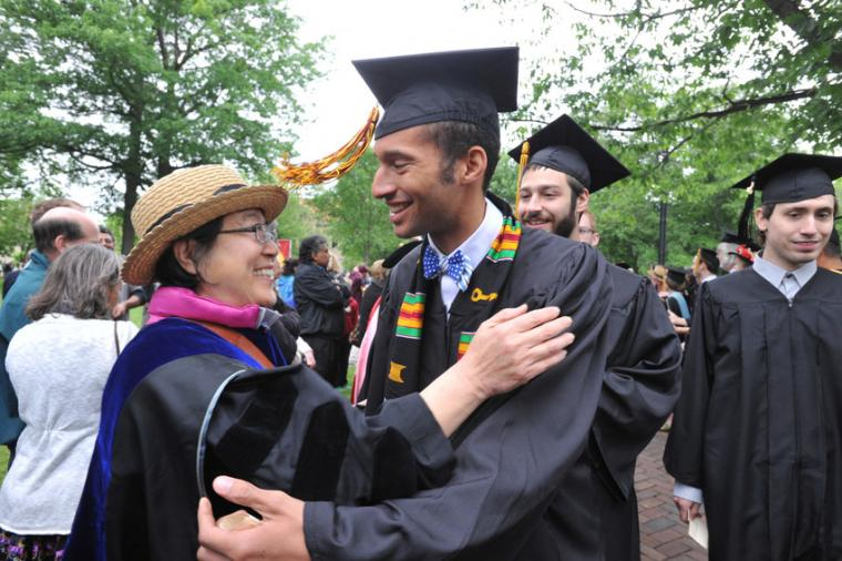 Two people in commencement regalia embrace as others look on