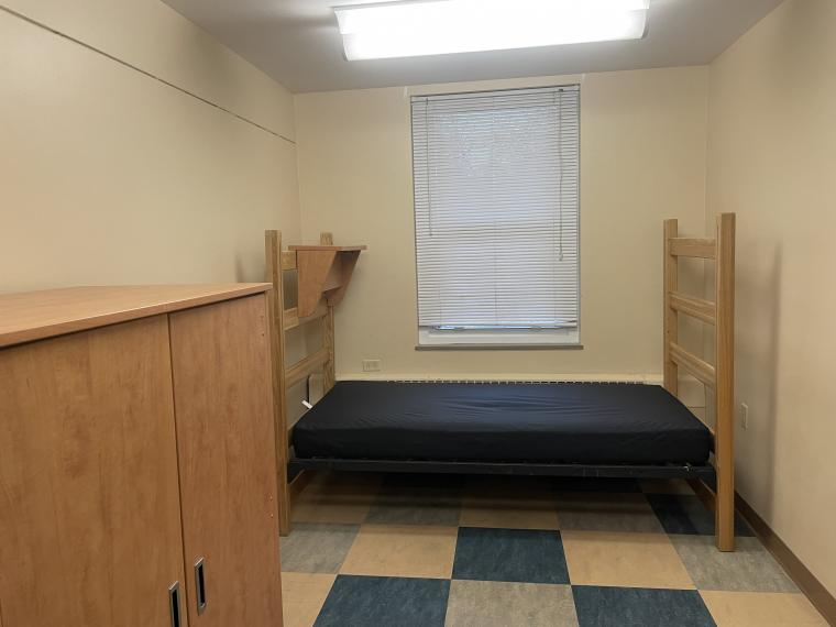 The picture shows one half of a bare divided double dorm room. At the back of the room, a bare blue mattress lays on top of its bed frame and a cabinet is placed on the left wall. No decorations or belongings are inside of the room.