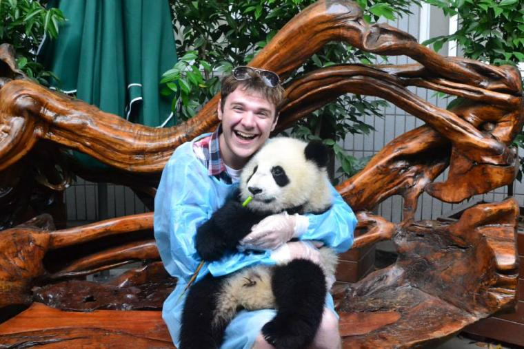 Photo of a man cradling a panda while seated on a stylized wooden bench