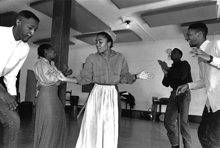 Photo of the ensemble rehearsing the call and response dance Juba, reminiscent of the Ring Shouts of the African slaves, Joe Turner's Come and Gone, by August Wilson, Directed by Caroline Jackson Smith, then artist-in-residence, Feb 1991