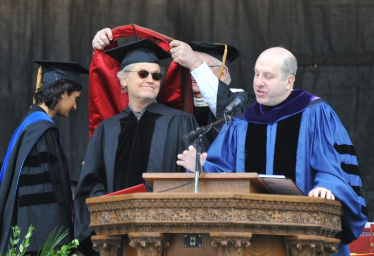 One man places a academic stole around the shoulders of another while a third speaks at a podium