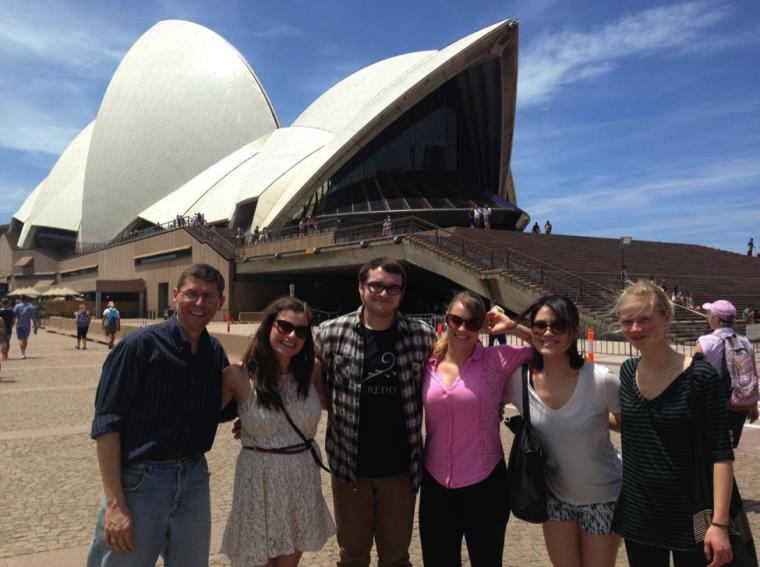 Six people pose in front of a stylized building on a sunny day