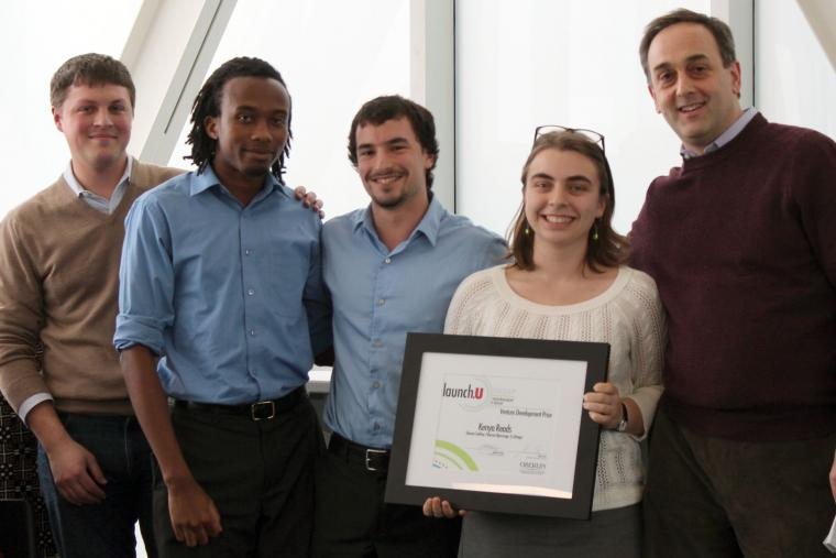 Photograph of five people; 4 men and one woman. The woman is holding a framed award.