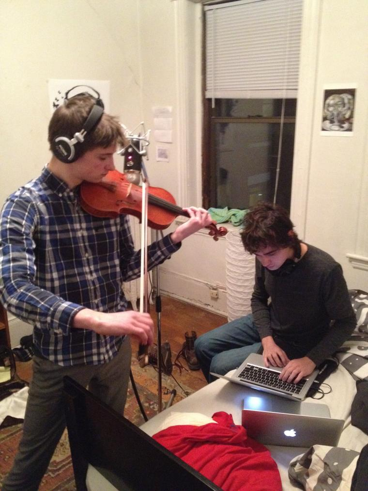 One person performs violin while another operates recording equipment in a bright room