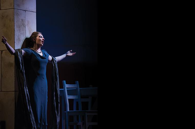 A lone woman sings while leaning against a pillar with arms extended