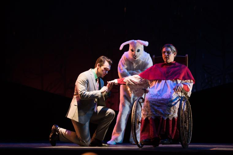 Photograph of three people on stage. One person is in a rabbit costume. The other is in a wheelchair and someone is kneeling on the side of this person and looking at their hand.