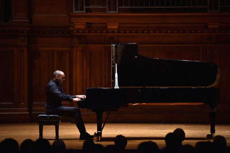 A man performs piano on stage for an audience