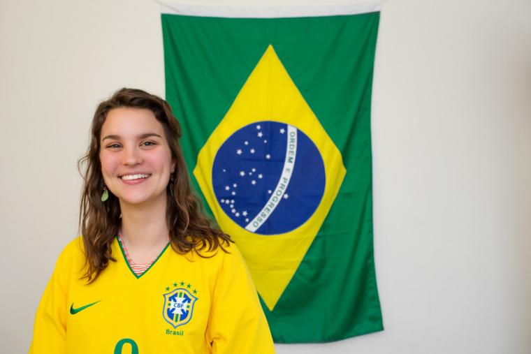 A woman smiles beside the Brazilian flag