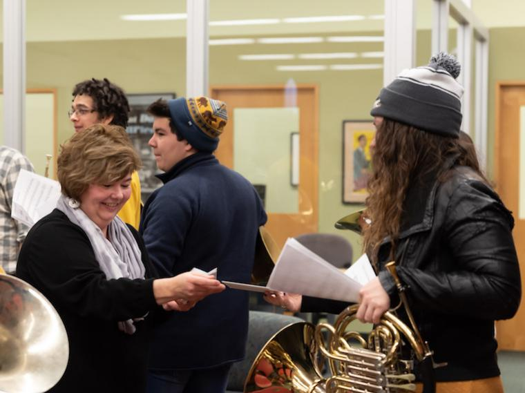 A woman gives a student a sheet of music.