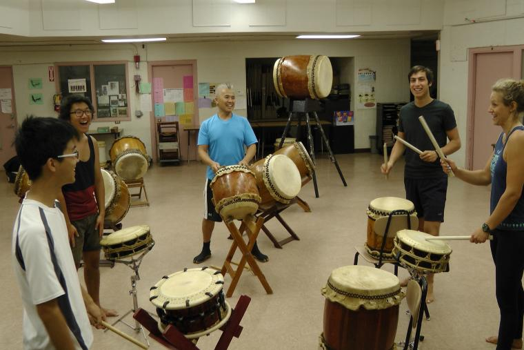A group of people laugh as they play standing drums