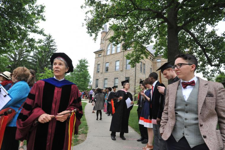 People in formalwear and commencement regalia line up along a sidewalk