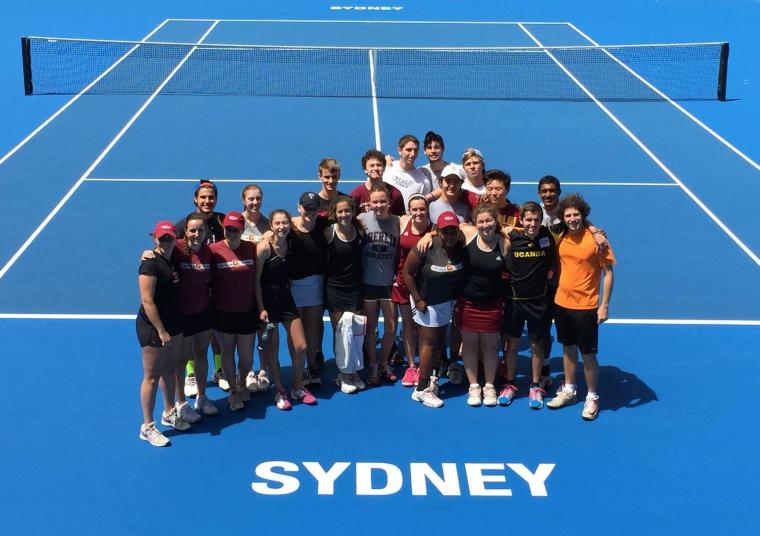 A group of people cluster for a photo on a tennis court