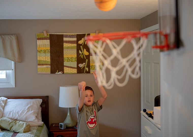 A boy playing basketball in his room.