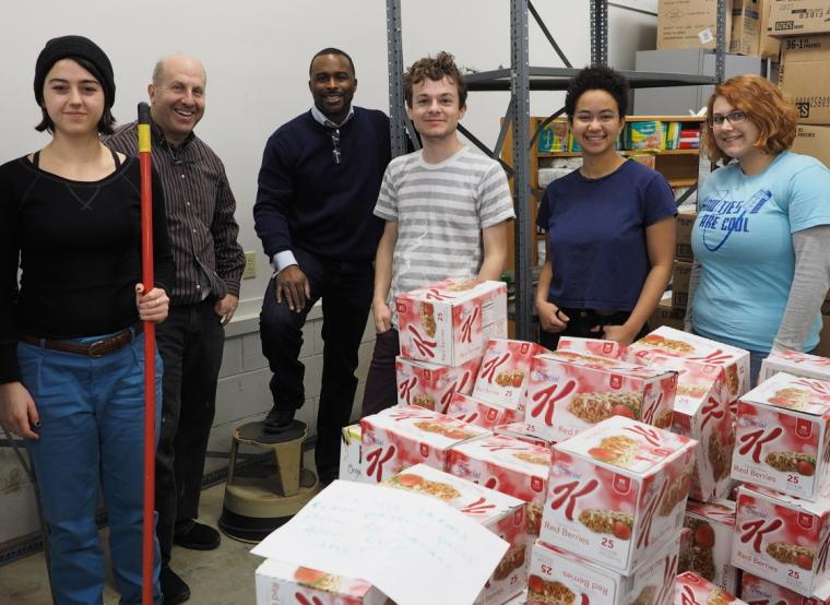 Six people smile and pose for a photo around stacks of cereal boxes