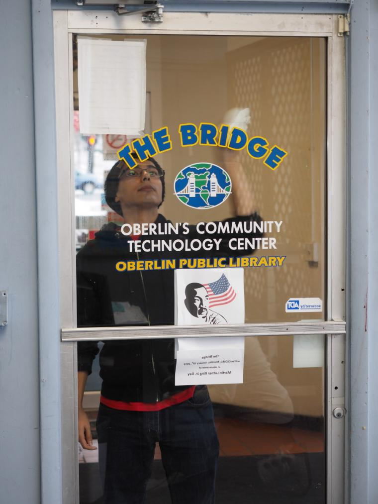 A person cleans the glass on the door to The Bridge Community Technology Center