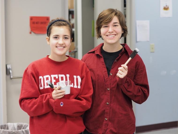 Two people pose and smile for a photo while holding small paint brushes