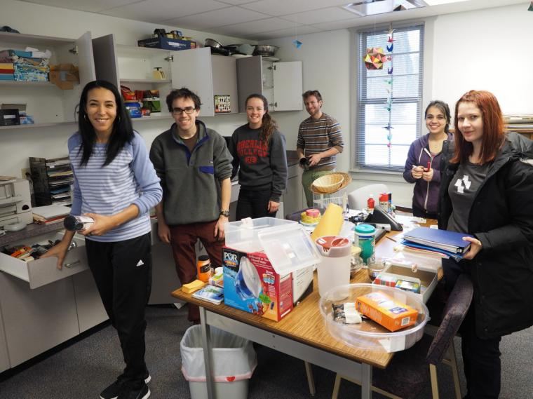 Six people stand around a table loaded with assorted supplies and beside open cabinets with more supplies