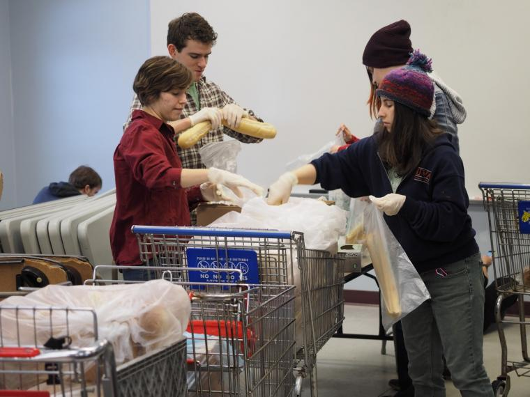 Four people load plastic bags with bread into shopping carts