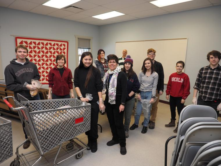 People pose for a photo in a plain room with folding chairs and shopping carts